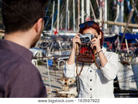 Young adult women taking photo with old single reflex camera