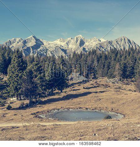 Frozen mountain lake at autumn meadow. Velika planina, Slovenia.