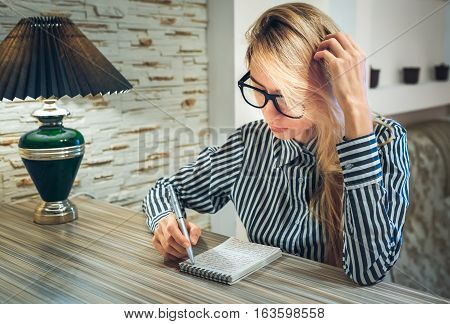 Girl Sitting At The Table And Writes In A Paper Notebook Amounts To A List And Thinking