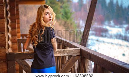 girl with long curly hair light wheat color is on the balcony of a wooden house in the woods