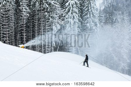 snow cannon throws on the ski runs. The skier standing on a among the snow covered firs in the forest and looking at the snow gun