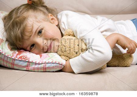Little girl with bear on sofa