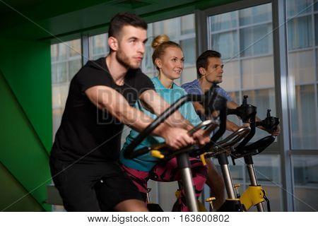 Group sportsmens on stationary bike in gym