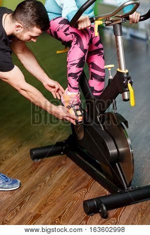 Girl on stationary bike engaged with coach