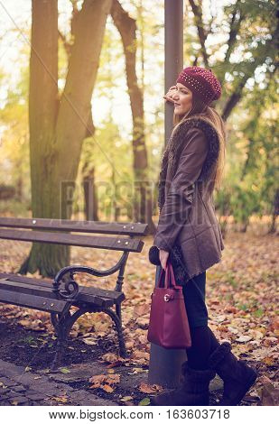 Stylish young woman in an autumn park standing alongside a rustic wrought iron and wooden bench leaning on a pole waiting for somebody