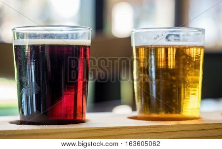 Two beer samplers in small glasses - one a dark beer while the other is a light beer.