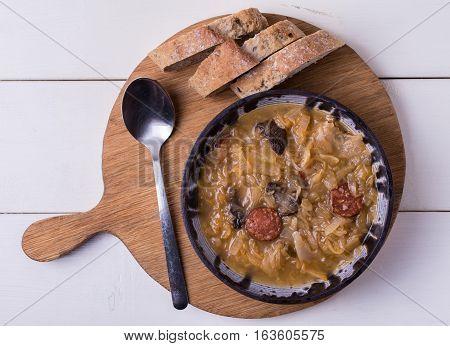 Slovak national christmas cabbage soup kapustnica with mushrooms on white background.