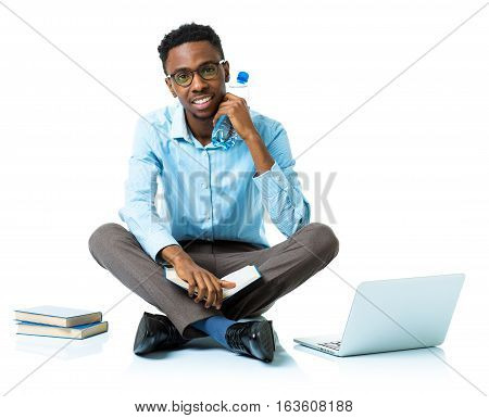 Happy african american college student sitting with laptop books and bottle of water on white background