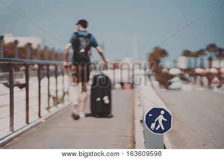 Blurred silhouette of a man with huge luggage bag going over narrow special pathway on sunny summer day with clear sky in Barcelona special Icon means path for people with luggage