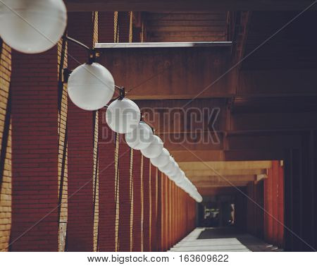 Round white ceiling lamps regularly going far into distance near brick columns of residential house Barcelona sunny day Spain