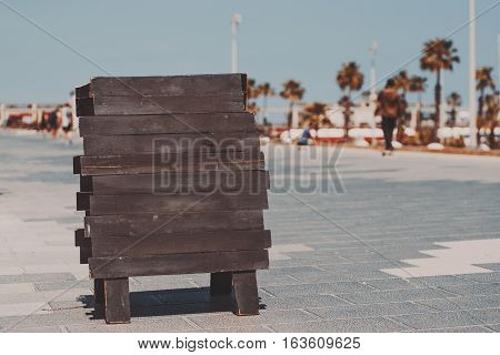 Mock up of wooden black planking banner staying on paving stone in Barcelona beach Barceloneta on summer sunny day with palms people and teal sky in blurred background