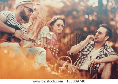 Best friends enjoying picnic together.Happy friends in the park having picnic and playing guitar on a sunny day.
