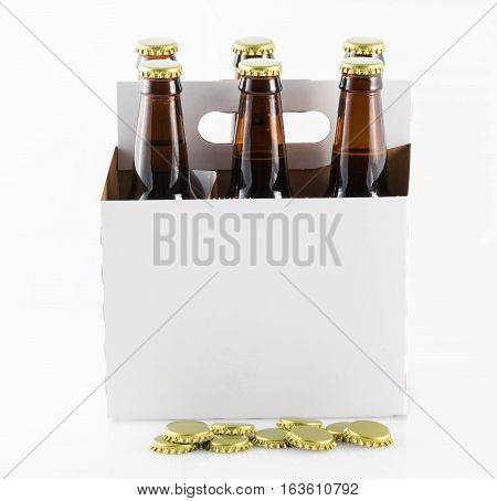 Six beer bottles in cardboard container with gold caps with side of carrier facing camera and bottle caps on table