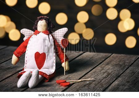 Angel a soft toy with heart sitting on old wood background. Valentine concept.