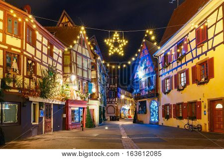 Traditional Alsatian half-timbered houses in old town of Colmar, decorated and illuminated at christmas time, Alsace, France