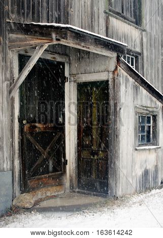 Side screen door access to dirty white barn during December snowstorm