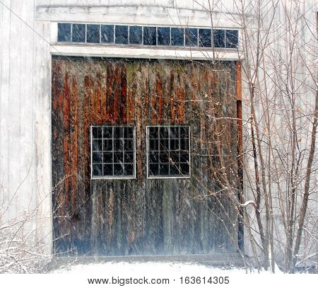 Mottled Brown barn doors to a dirty white New England Barn during a December snow storm