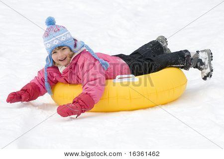 Little girl sliding downhill on tube