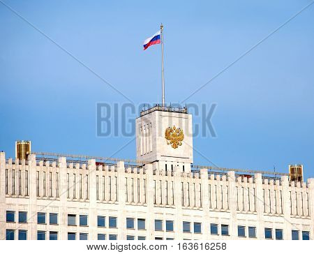 White house. Top of Russian house of parliament in Moscow with flag and coat of arms close up