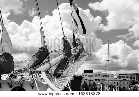 Details of bowsprit and gathered sail of the tall ship on the cloudy sky background. Concepts: prosperity, optimism, positive, future