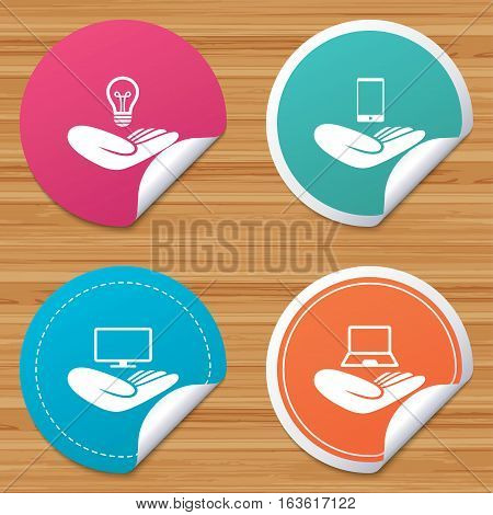 Round stickers or website banners. Helping hands icons. Intellectual property insurance symbol. Smartphone, TV monitor and pc notebook sign. Device protection. Circle badges with bended corner. Vector