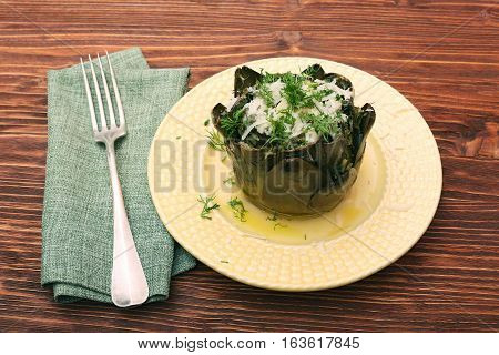 Baked artichoke with cheese on wooden background
