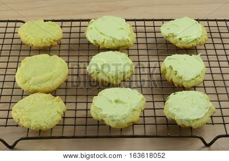 Key lime sugar cookies, some with icing, others waiting to be frosted, on cooling racks