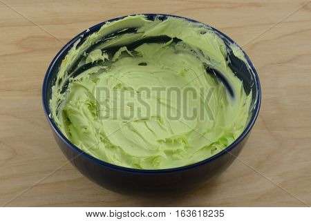 Homemade lime green frosting in blue bowl on wooden table
