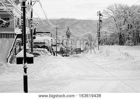 A quiet, early morning street in Myoko. Snow-covered buildings, cars and roads from the overnight snowfall. Distant mountains show the extent of the snowfall. Black and white image.