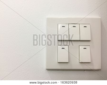 Light electric switches on white wall background