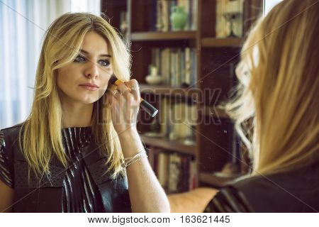 Portrait of a pretty blond woman tidying herself at the mirror and applying make-up to her skin