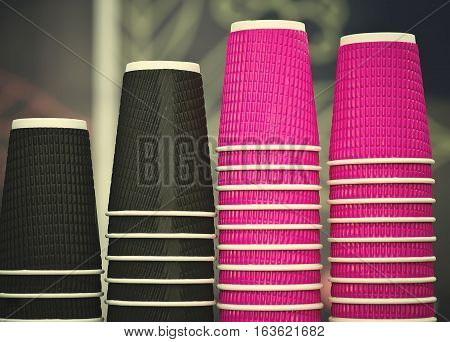 Black and pink craft paper coffee cups in cafe on wooden table. Lifestyle, coffeeshop concept.