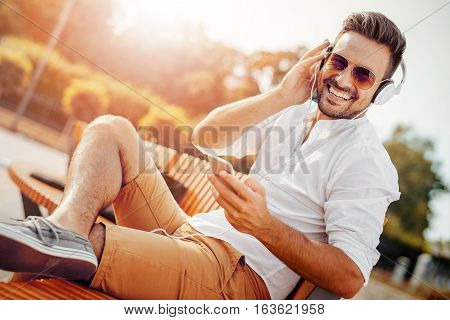 Portrait of smiling young man.Young man sitting outdoors listening to music.