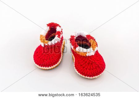 Little baby shoes. Kids knitted shoe handicraft on white background.