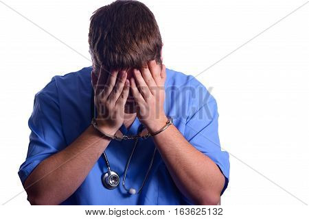 Male Professional in Handcuffs with Stethoscope Covering Face in Shame