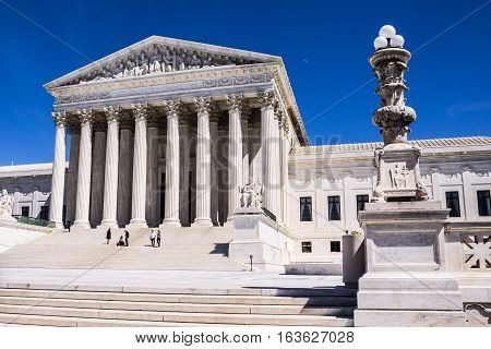 WASHINGTON, D.C. - APRIL 6, 2014: Tourists on the steps of the main entrance of the Supreme Court building, completed in 1935.