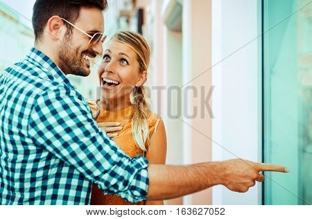 Young man showing something in the shop window to his girlfriend