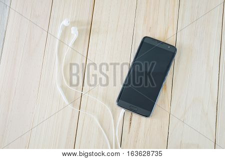 Smartphone or mobile phone with mobile headsets or small talk or ear phone on wood background and texture