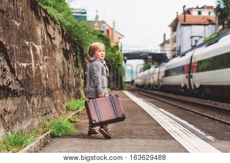 Adorable little boy on a railway station, waiting for the train with suitcase