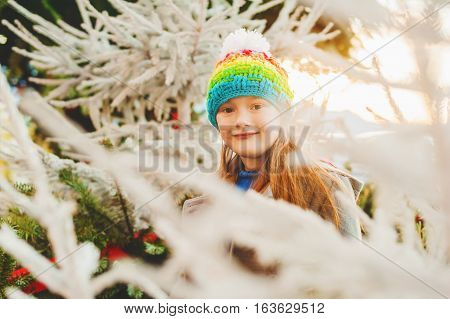 Sweet little girl wearing colorful hat, standing between christmas trees at sunset