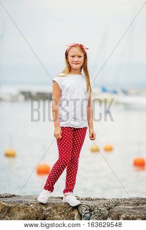 Happy 9 year old girl having fun outdoors, playing by lake on a nice warm sunny evening, wearing white t-shirt and shoes, red polka dot trousers and headband. Image taken at Lake Geneva, Switzerland