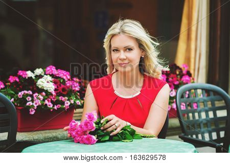 Outdoor portrait of beautiful blond woman holding bouquet of pink roses, resting in cafe