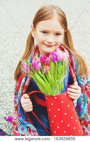 Spring close up portrait of 7 year old girl holding polka dot watering can with fresh pink tulips