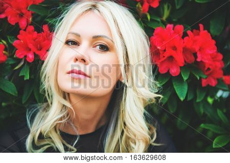 Beautiful blond woman with red flowers on background