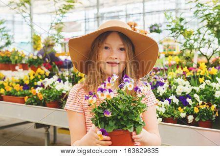 Adorable little girl choosing flowers in garden center