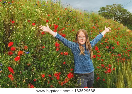 Outdoor portrait of adorable little blond girl of 8-9 years old in poppy field, arms wide open