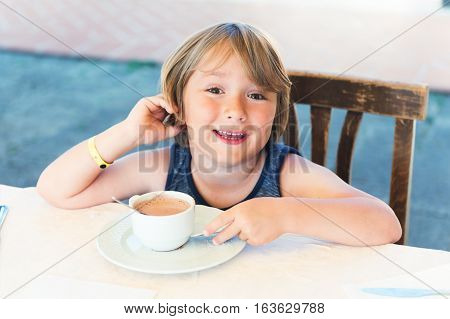Outdoor portrait of a cute little boy drinking hot chocolate in cafe