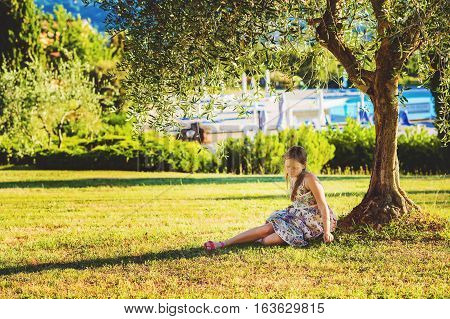 Little girl resting under olive tree on a very hot day in summer