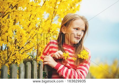 Spring portrait of adorable little girl wearing red stripe pullover