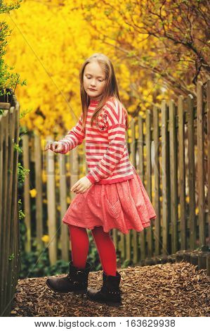 Spring portrait of adorable little girl wearing red stripe pullover and skirt against yellow forsythia flowers